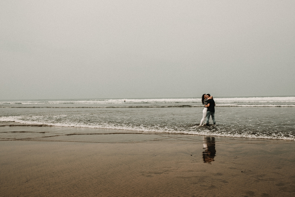 couple having a cuddle in the wave in bude