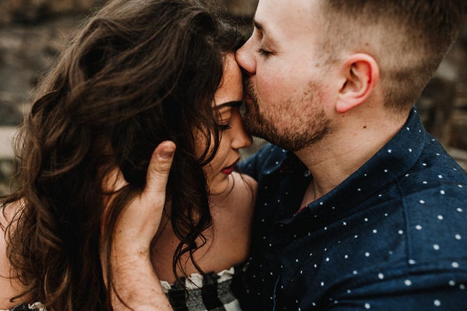 couple kissing on rocks cornwall beach