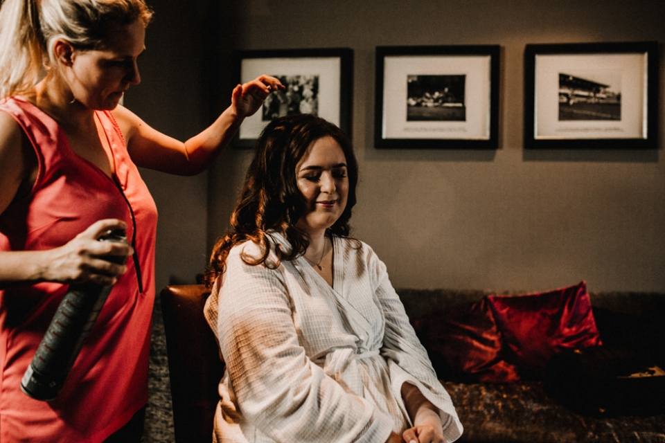 bride having her hair finished on her wedding morning