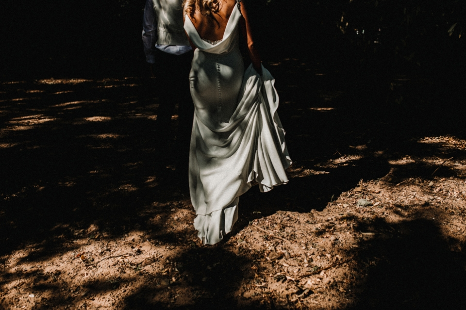 bride and groom walking into the forest
