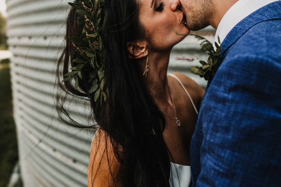 close up of bridge and groom kissing next to a barn container at Merris court
