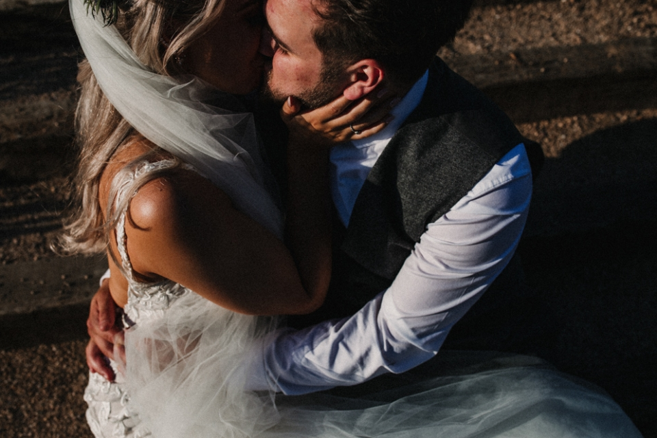 bride and groom kissing on the steps at the west mill wedding venue
