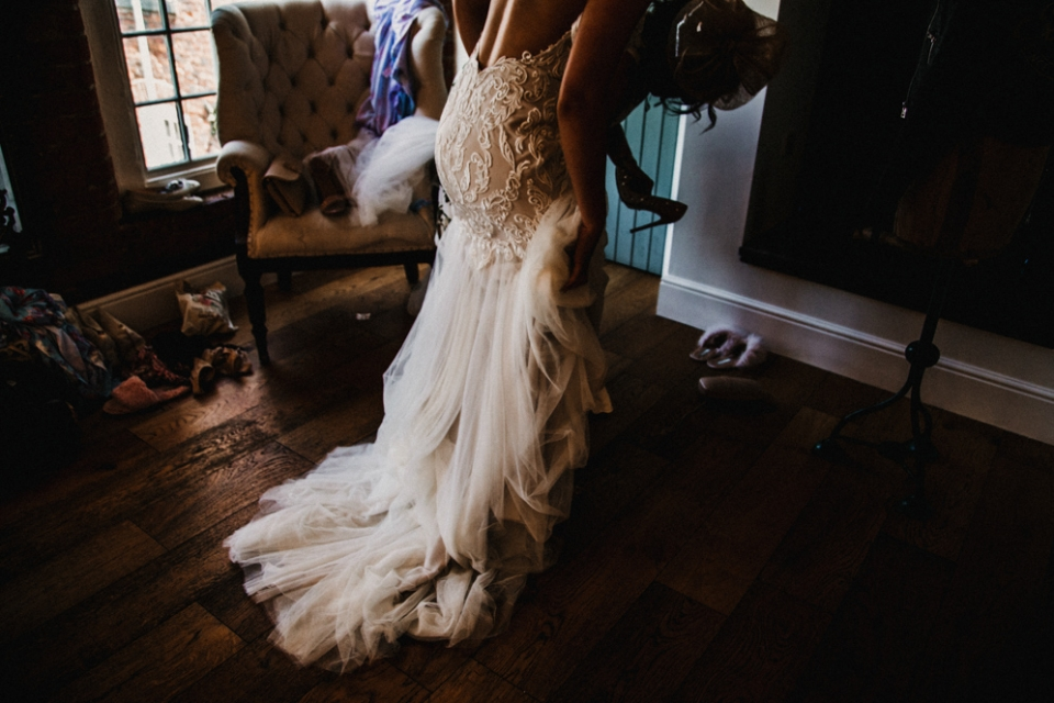 bride putting her dress on during bridal preparations