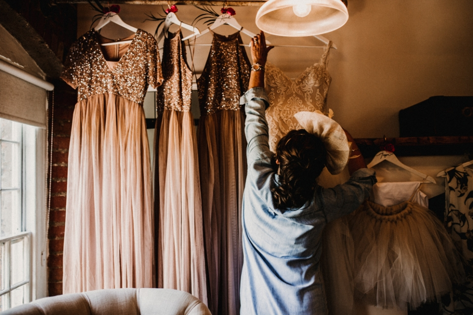 mother of bride reaching for brides dress