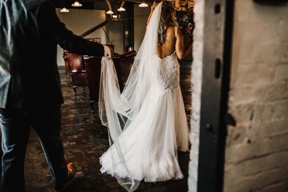 groomheping wife with her dress at the stairs in west mill wedding venue