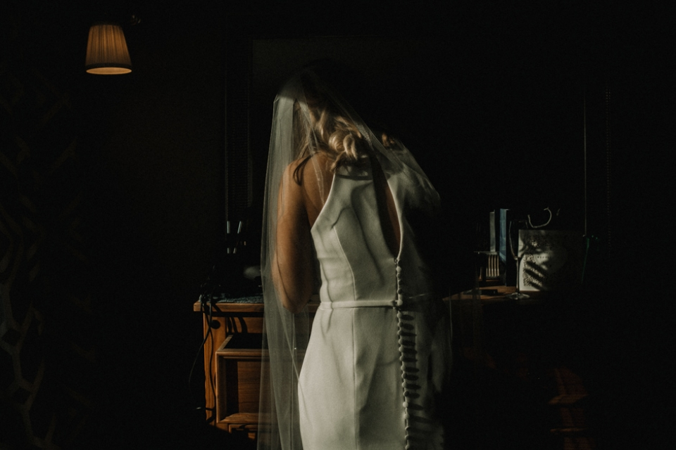 bride putting her lipstick on in the mirror , light catching her veil