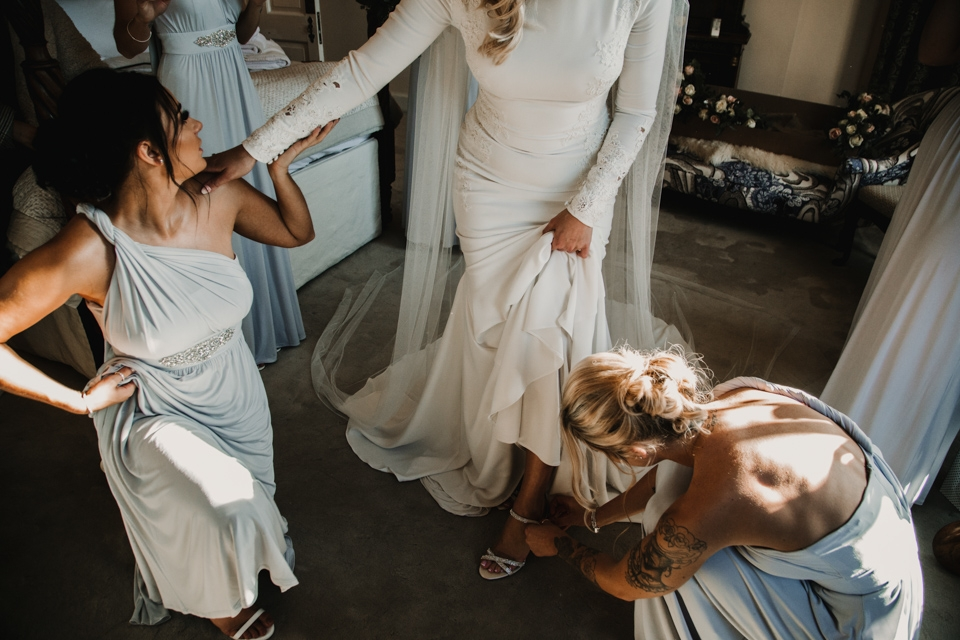 bridesmaids helping bide into her shoes