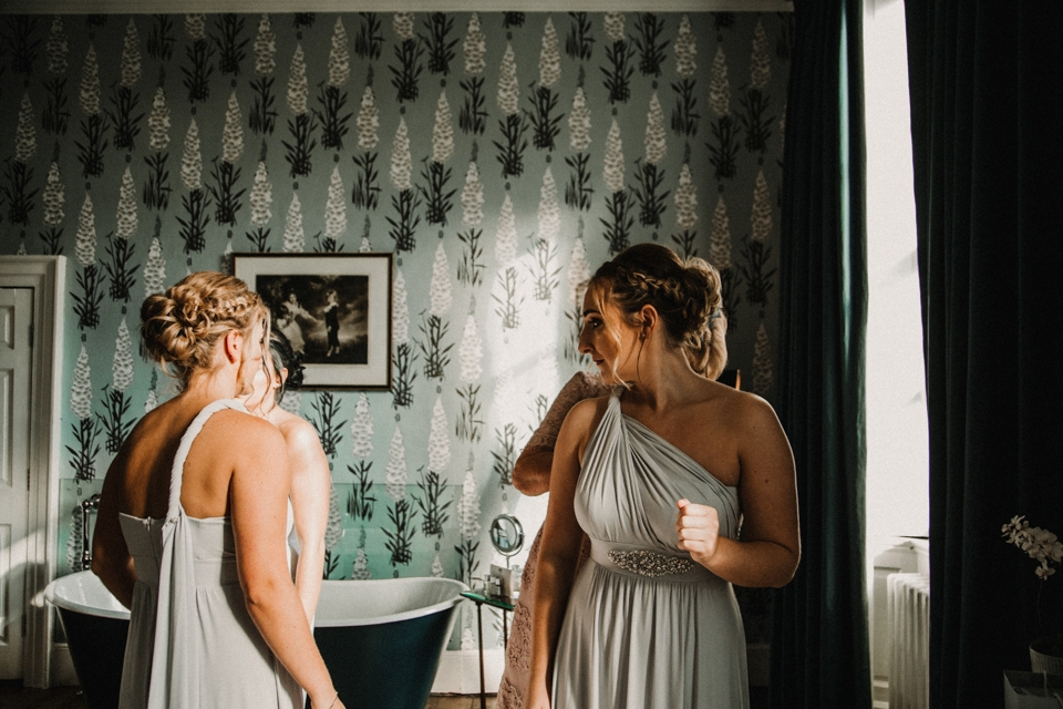 bridesmaids looking in mirror in their dresses