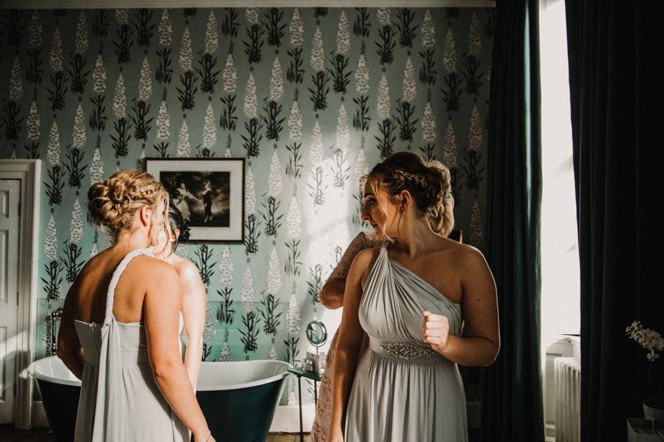bridesmaids looking in mirror in their dresses