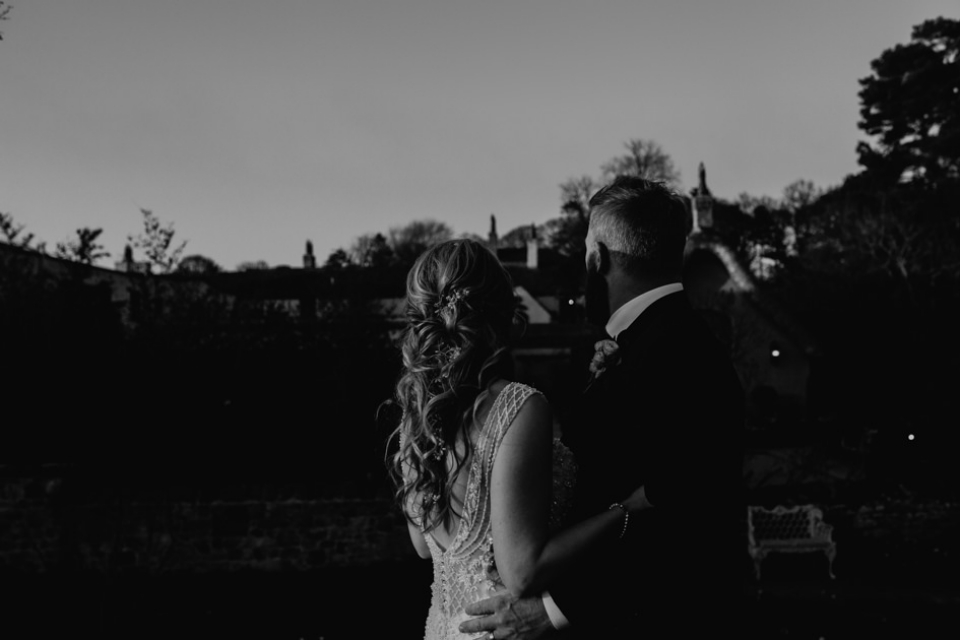 black and white portrait of bride and groom outside gardens in le petit chateau