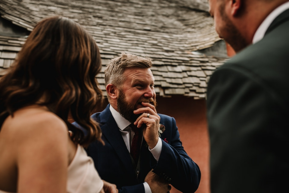 groom enjoying a giggle with friends during wedding reception