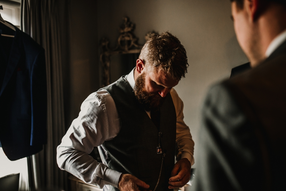 groom getting dressed during groom prep