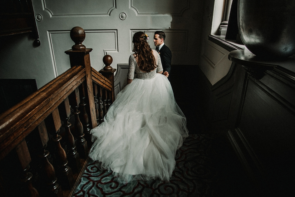 bride and groom inning down the stairs for some alone time