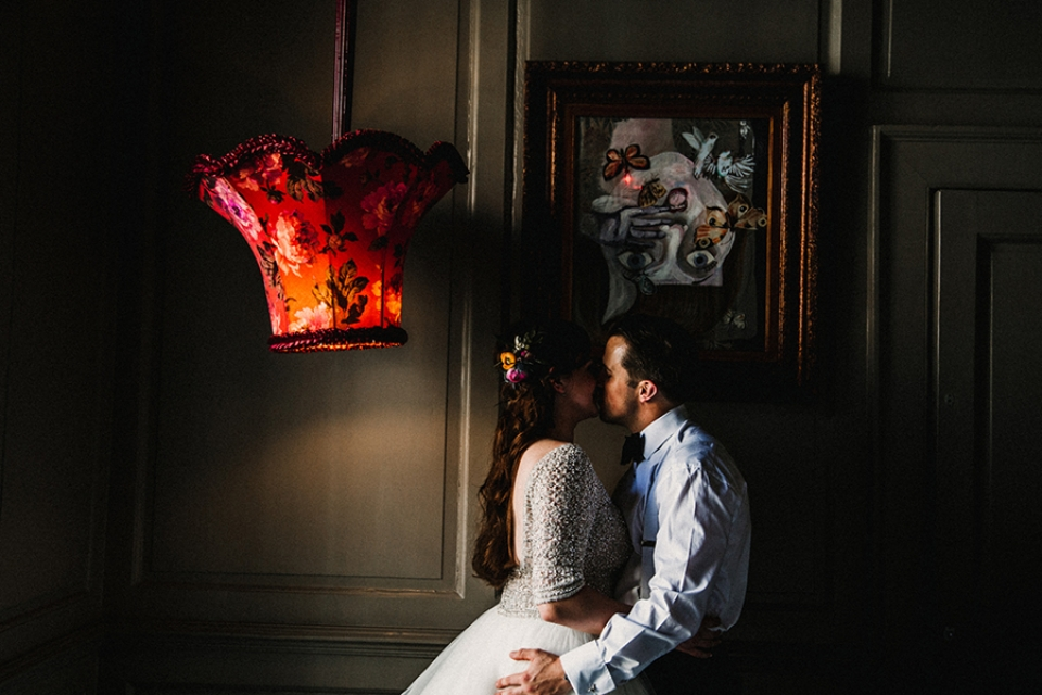 bride and groom having a kiss in the alice and wonderland themed room.