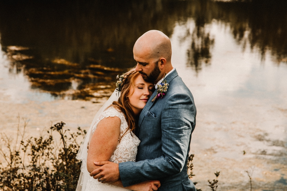 couple cuddles bride and groom at buckland house boating lake