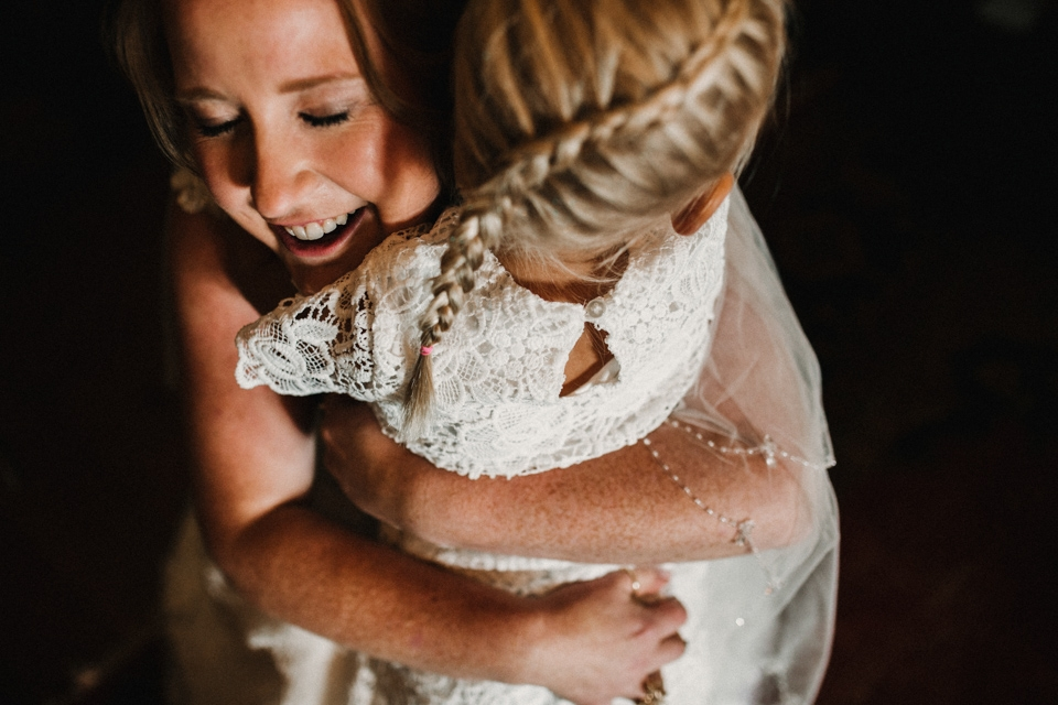 bride giving the flower girl a hug