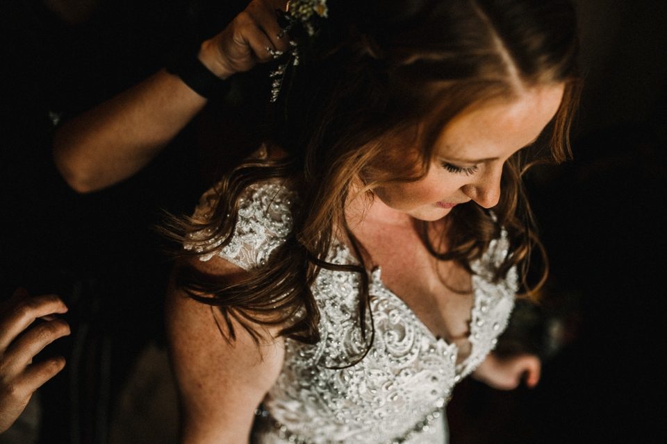 bride dressing into her wedding gown