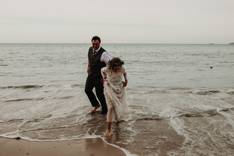 bride and groom playing carbis bay beach on wedding day