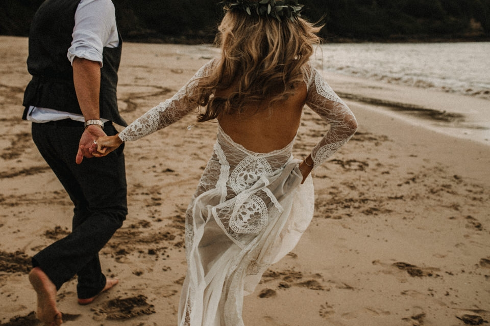 bride and groom running on the beach , playing in the water in cornwall