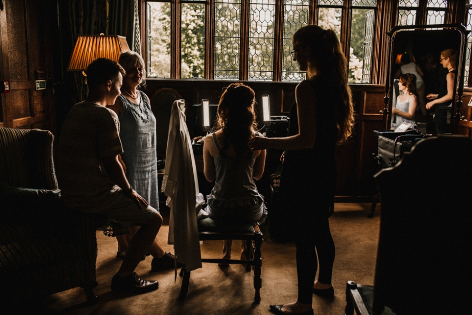 bridesmaids getting ready together with the bride at the castle , Kent