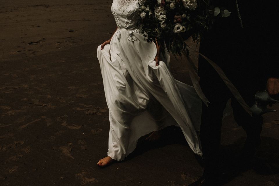 bride walking barefoot in the sand