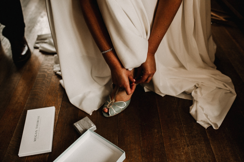 bride putting on her bridal shoes