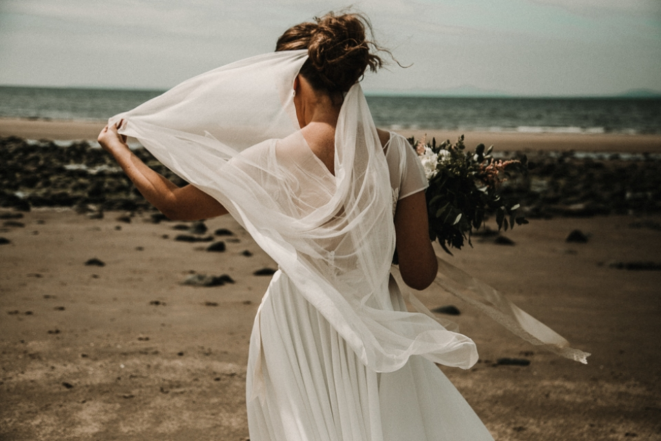 bride playing with her veil on the beach