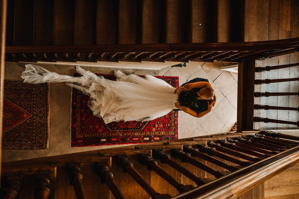 bride and groom kissing at the bottom of the stairs