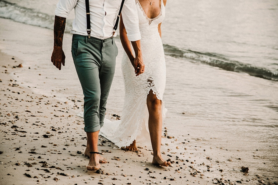 bride and groom strolling on the beach