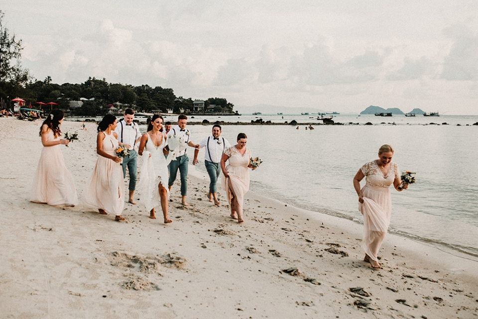 bridal party strolling on the beach