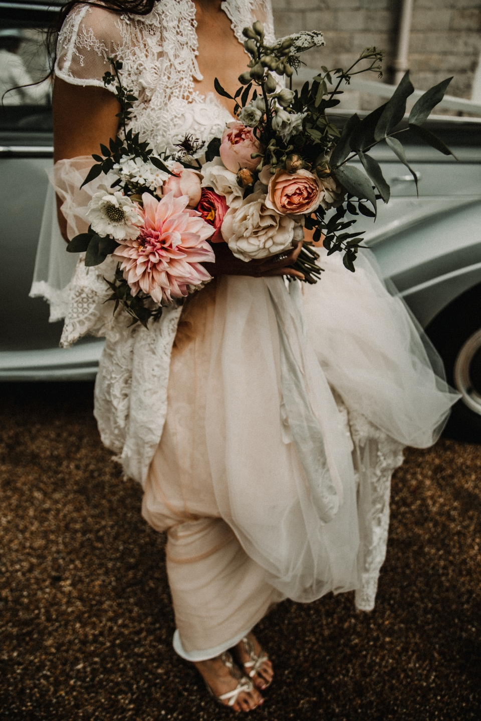 bride holding her flowers in front of her vintage bentley