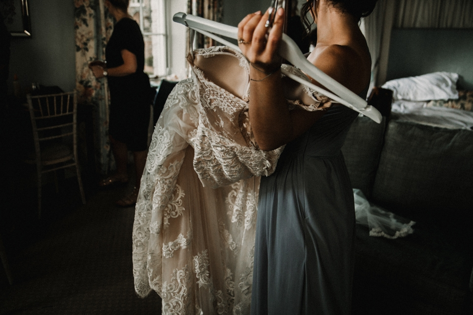 bridesmaids getting wedding dress ready for bride