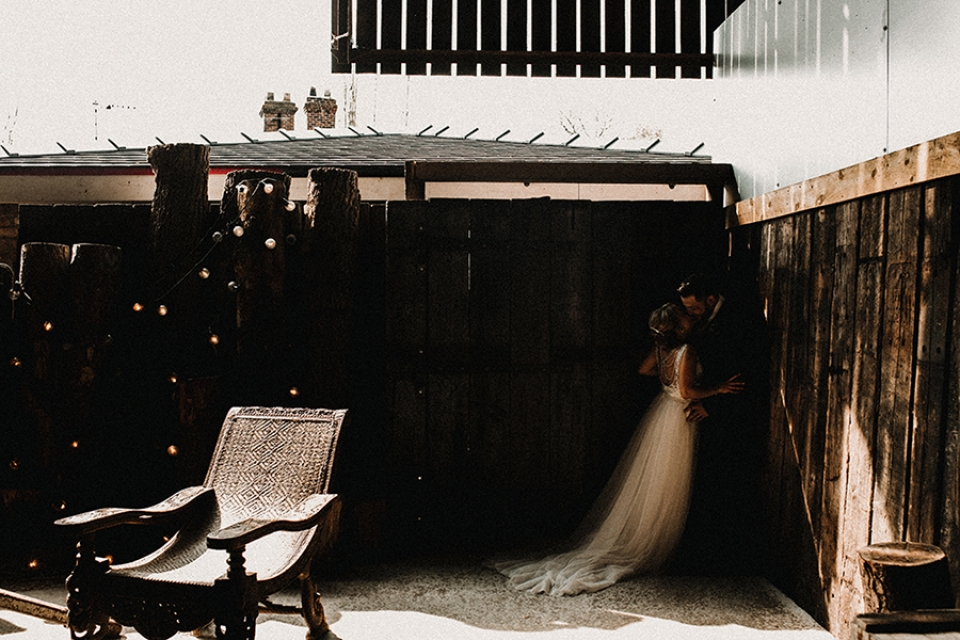bride and groom having a kiss in the corner of the wedding barn