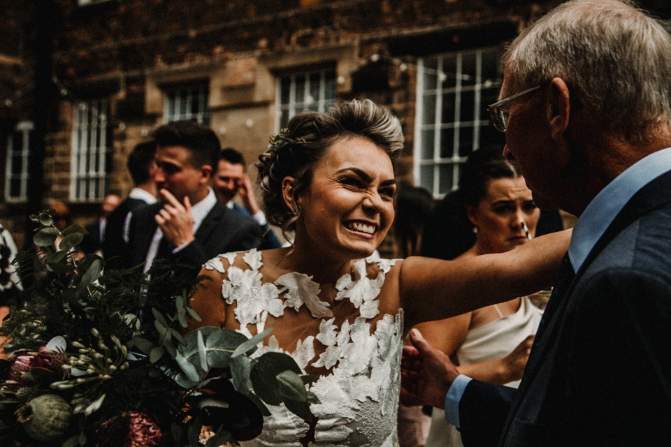 bride embracing her father on their wedding day while he congratulates her.